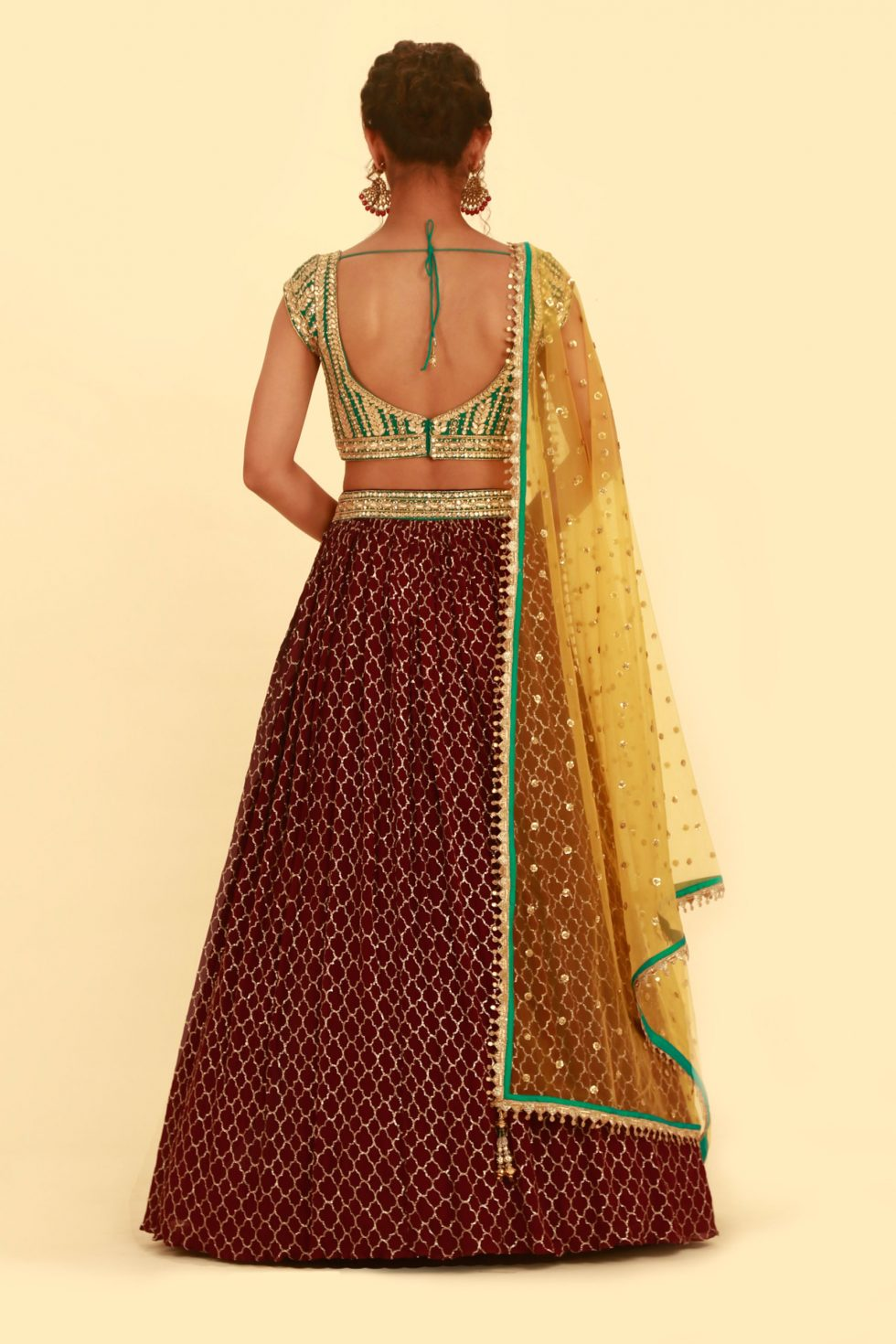 Burgundy wine lehenga with contrast green choli and contrast yellow dupatta with gold embellishments