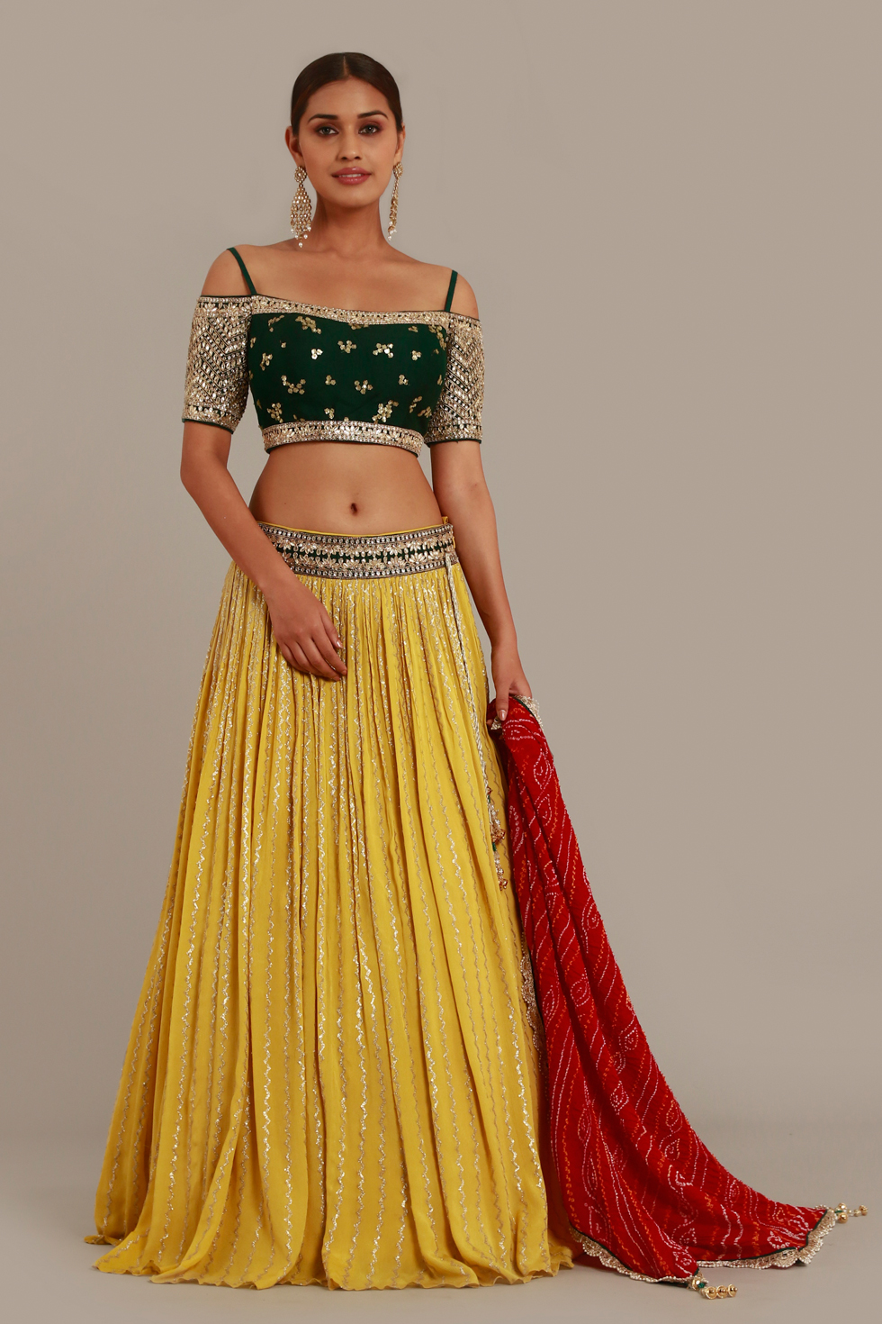 Deep yellow lehenga with contrast forest green choli with gota work and classic bandhani dupatta