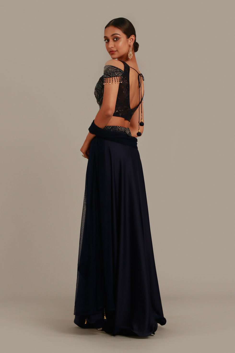Midnight blue draped palazzo pant set with matching cold shoulder cut out crop top and silver details with tassels and matching dupatta