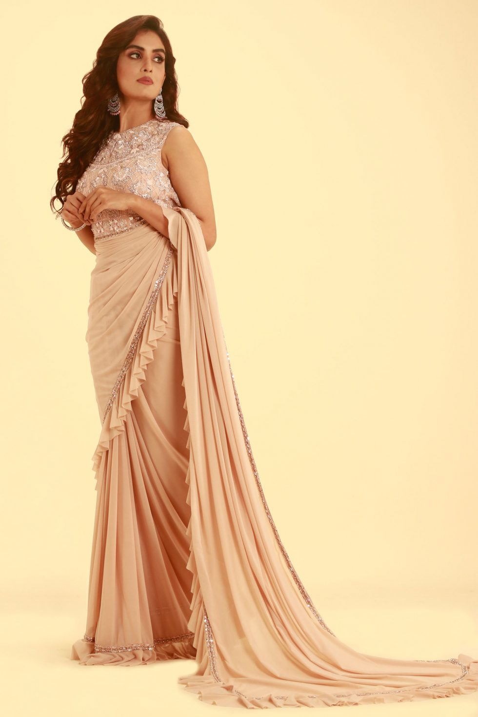 Petal pink ruffle saree with cut out embroidered blouse and matching tassels