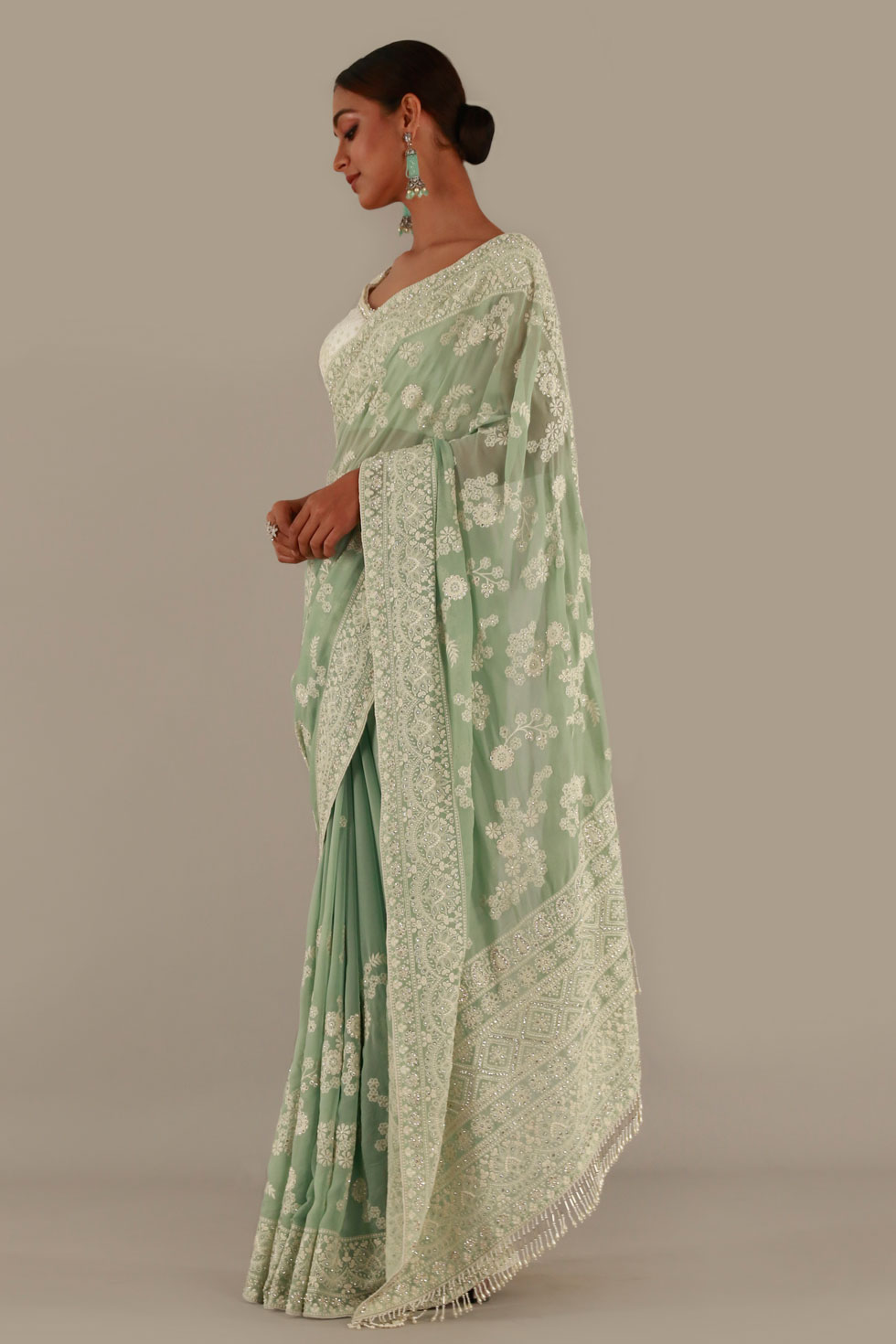 Mint green classic saree with contrast ivory choli and pearl and stone embellishments