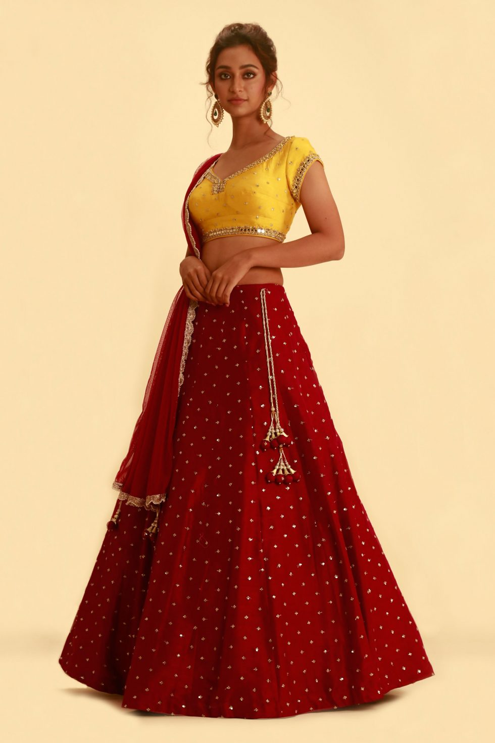 Contrast yellow and deep red lehenga set with mirror highlights and gold embellishments
