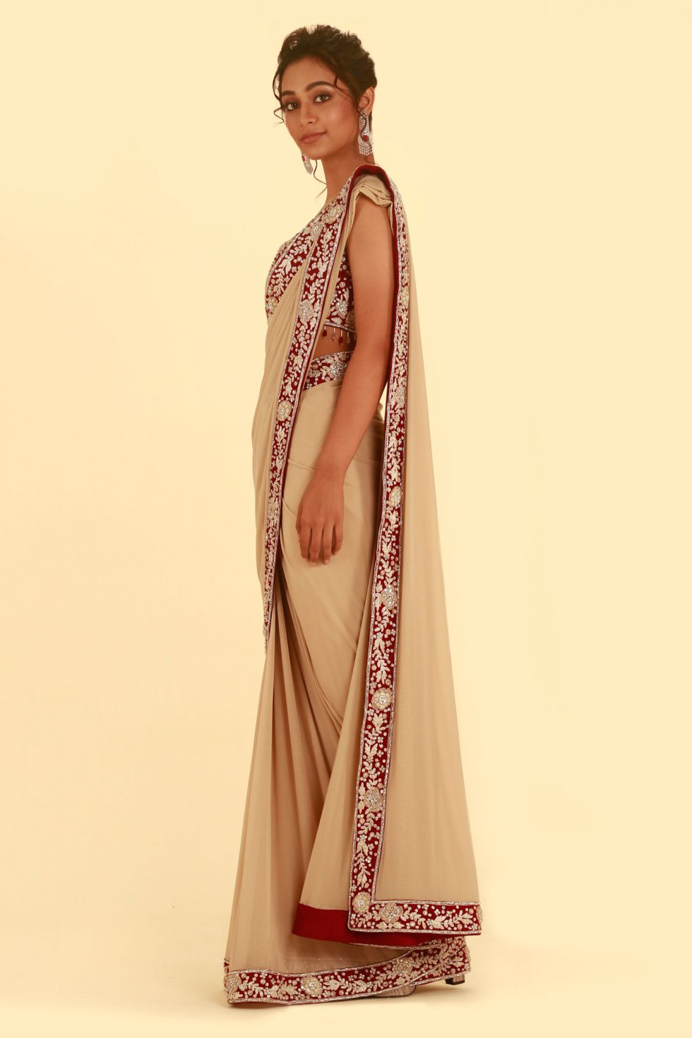 Beige gold saree with contrast Red maroon choli and border with silver gold details and tassels