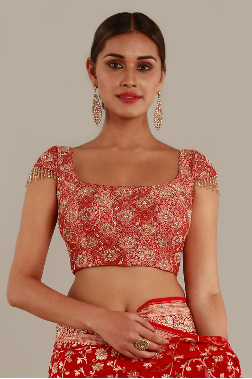 Fiery red choli with gold highlights and tassels