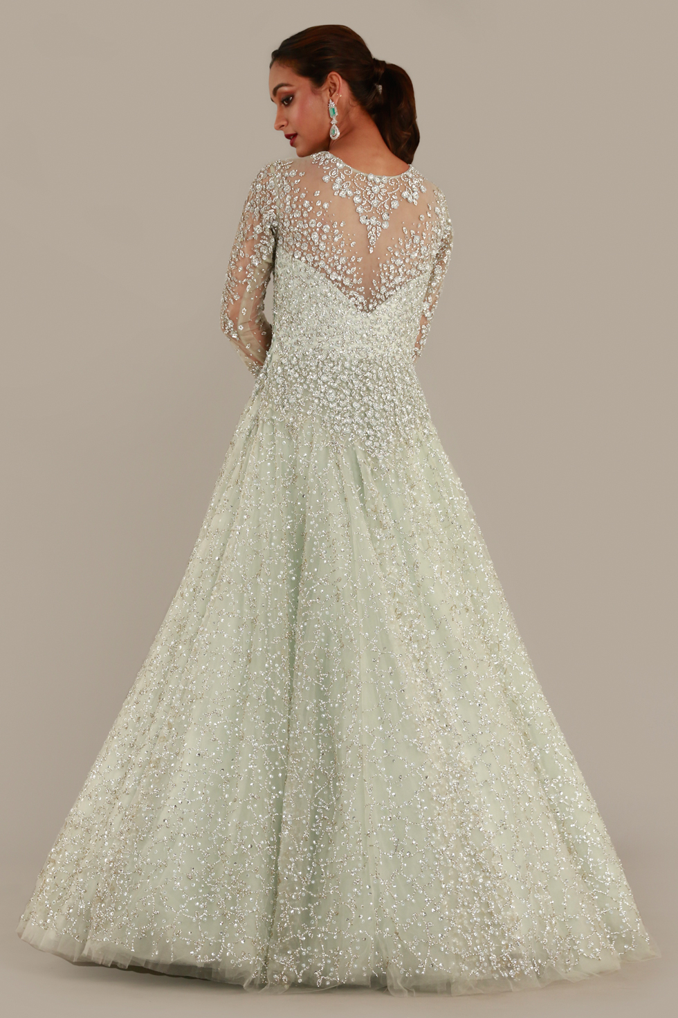 Pastel green tulle gown with illusion sleeves, silver embroidery and stone work embellishments