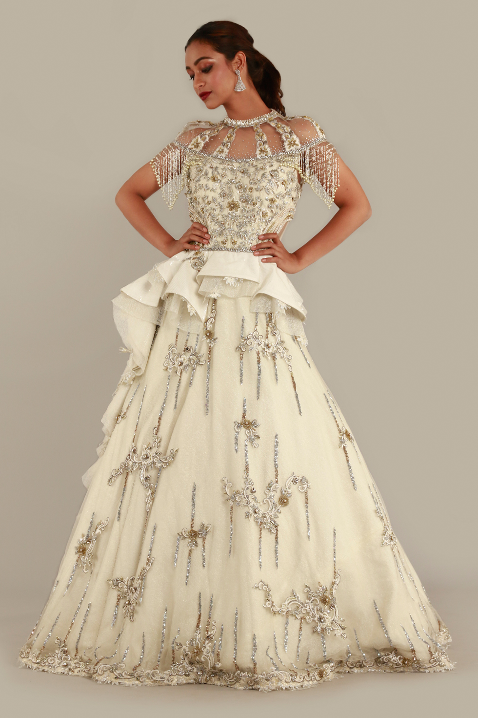 Pearl white gown with peplum waist, gold and silver embroidery, cut out details and tassels on the sleeves