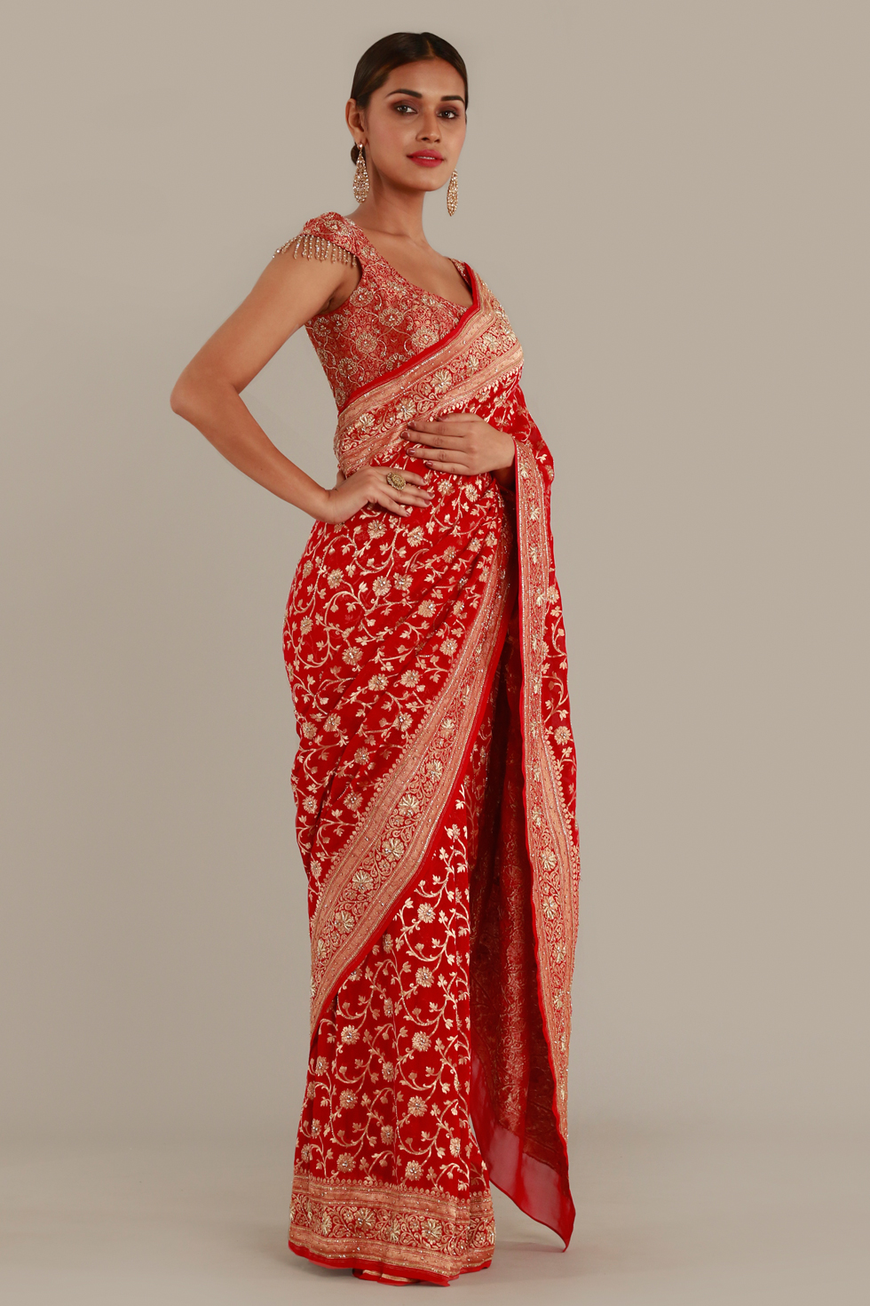 Fiery red saree with gold floral motifs, heavy border and matching blouse with gold embellishments and tassels