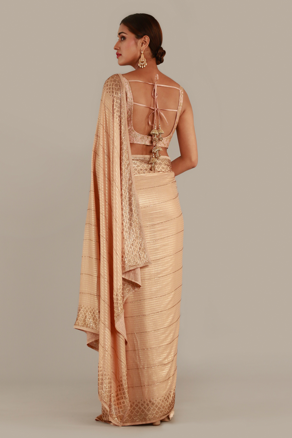 Pastel peach pink classic saree with gold details and matching blouse with gold neckline embroidery